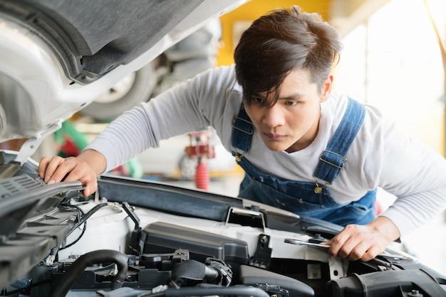 Механик работают в гараже. ремонт с ключом.