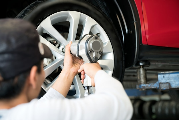 車のサービス - 車庫で働くオートメカニック。修理サービスとタイヤ交換。