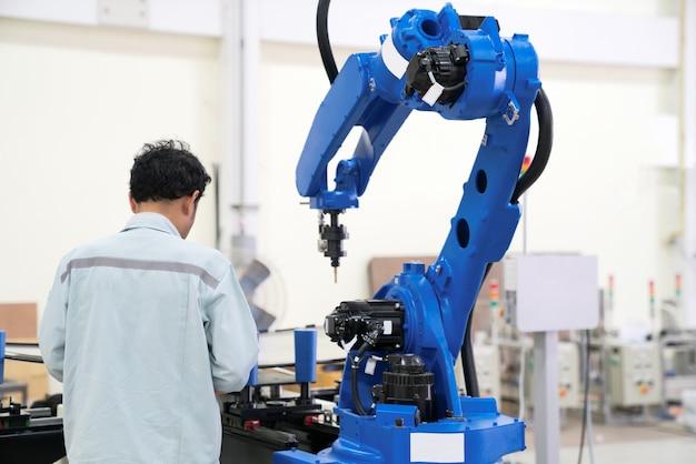 エンジニアの手は、スマートな工場の工業では、タブレット、重い自動化ロボットアームのマシンを使用して