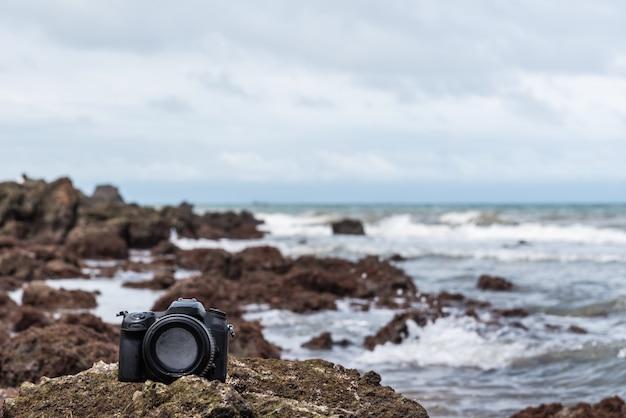 水の海の波から濡れている石のビーチでデジタル一眼レフカメラ