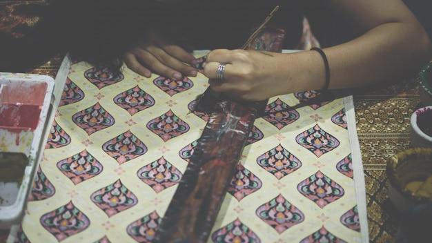 タイの芸術家がタイの絹を作るためのタイの芸術を描く
