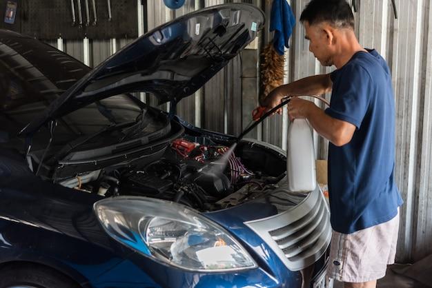 車のガレージで修理のために車のエンジンをチェックする