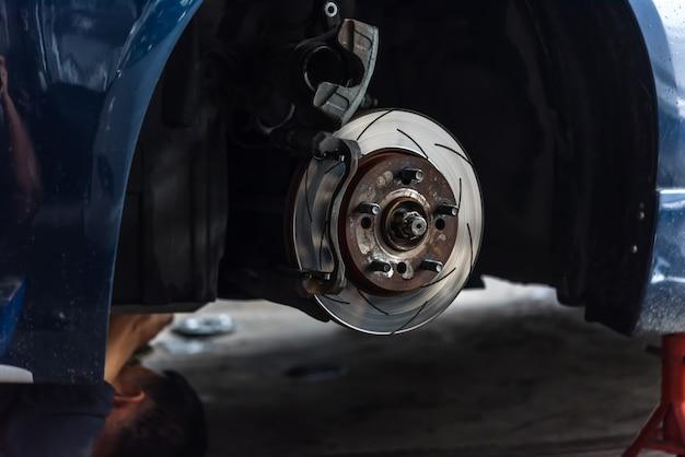 自動車整備士またはサービスマンがディスクブレーキとアスベストブレーキをチェック