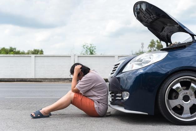 Женщина несчастна и мрачна из-за проблем с двигателем автомобиля