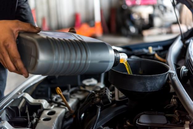 自動車整備士が新鮮な潤滑油エンジンオイルを充填