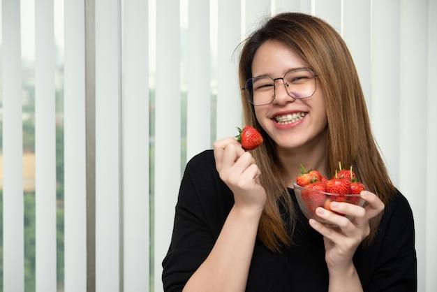 女性はジューシーなイチゴの赤いベリー果実を食べる