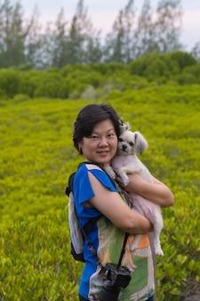 アジアの女性と彼女の犬はマングローブフォレストでポーズをとる