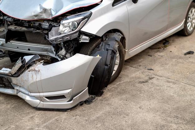 フロントのクローズアップの車は、ソフトフォーカスとバックグラウンドの光の上で偶然に傷ついています