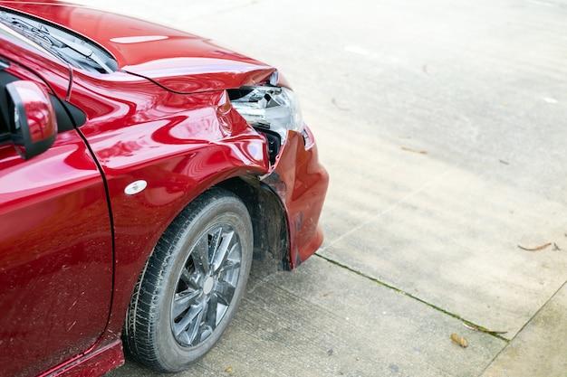 前のクローズアップの赤い車は偶然に損傷を受けています