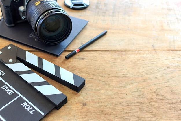 映画監督の机。カチンコ、本、木製のテーブルの上のデジタルカメラ