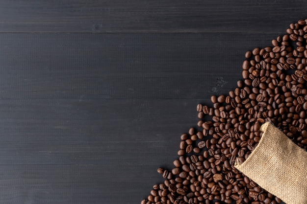 古い木製の背景に黄麻布の袋にコーヒー豆。上面図