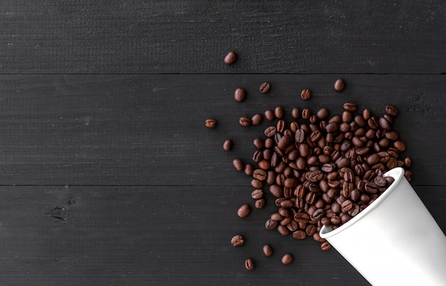 ホワイトペーパーカップと古い木製の背景のコーヒー豆。上面図