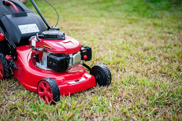 芝生の上の公園で芝刈り機を閉じる