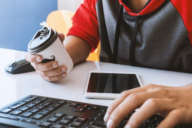 ビジネスの男性と机の上のコーヒーの紙コップはオフィスで働いています。