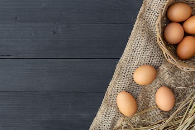 黒い木製の背景にクローズアップの卵。上面図