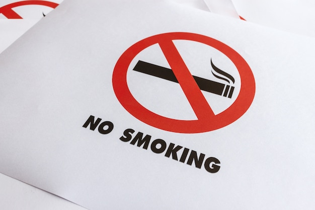 Крупным планом знак не курить на белой бумаге