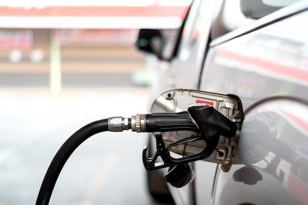 ガソリンスタンドの白い車に給油クローズアップ車