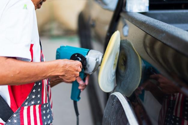 Крупным планом рука мужчина полирует черный автомобиль с полировщиком