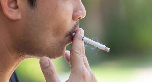 Крупным планом молодой человек курит сигарету