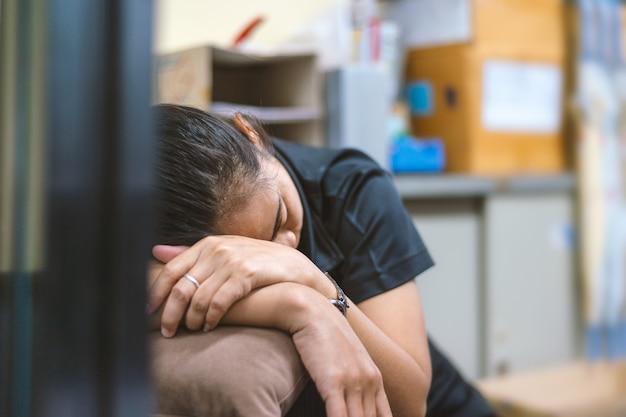 オフィスの机の上に眠っているクローズアップ若いビジネス少女