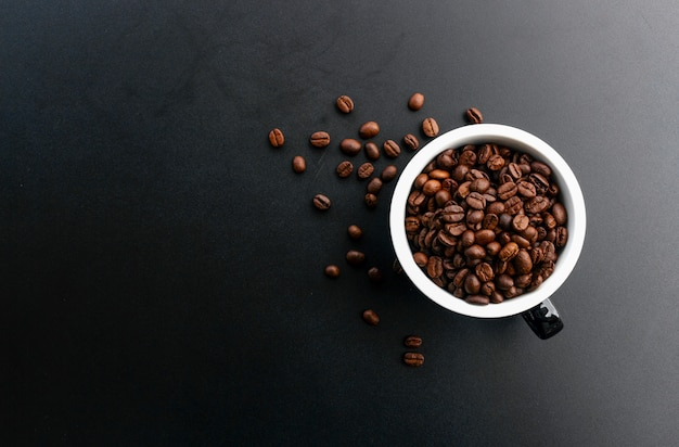 Кофе в зернах в чашке на черном фоне