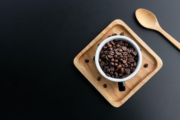 黒の背景の上にカップのコーヒー豆