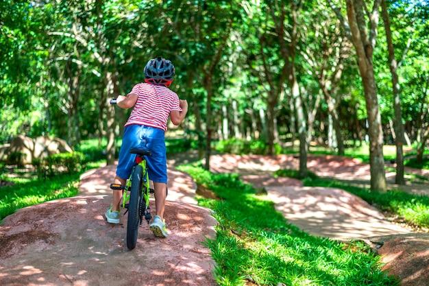 Молодой мальчик езда на велосипеде в саду