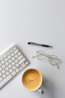 キーボード、ペン、メガネ、白いテーブルの上の熱いコーヒーカップのオフィスデスクワークスペースのトップビュー