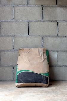 工事現場のワークスペースでレンガの壁にクローズアップモルタル袋