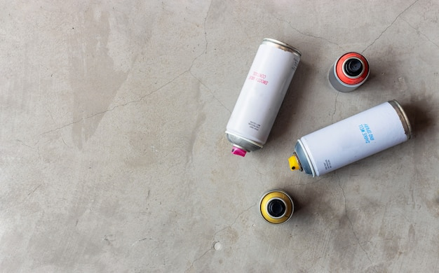 セメントの床にスプレー式塗料の古い缶をクローズアップ