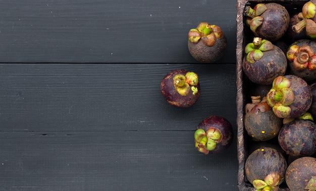 Плод мангустана крупным планом на черном дереве
