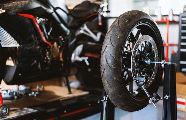 オートバイの修理。タイヤサービスセンターでクローズアップホイールバランシングマシン