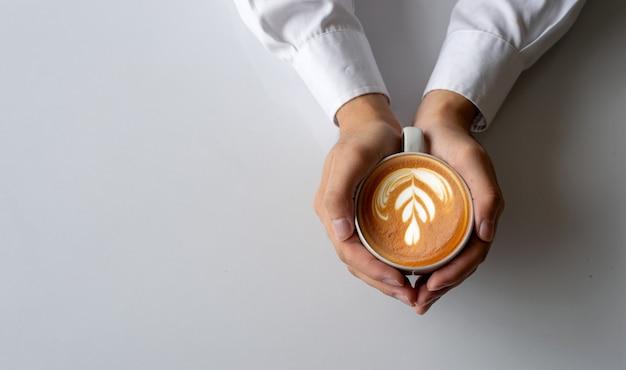 白いテーブル背景にコーヒーのカップを保持しているクローズアップ男の手