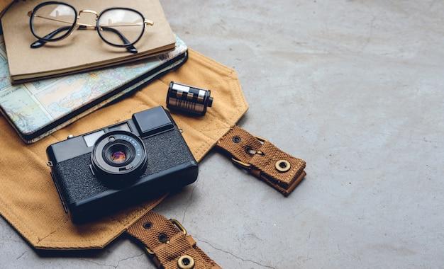 旅行のコンセプト。古いカメラフィルム、地図、本、旅行アクセサリー