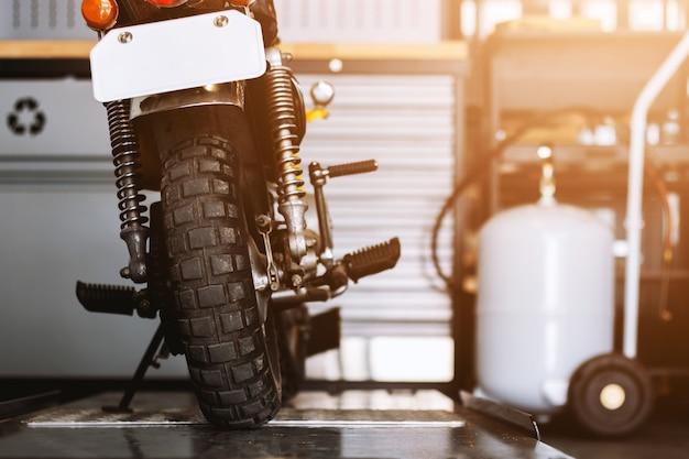 修理工場に立っている古典的なオートバイの背面