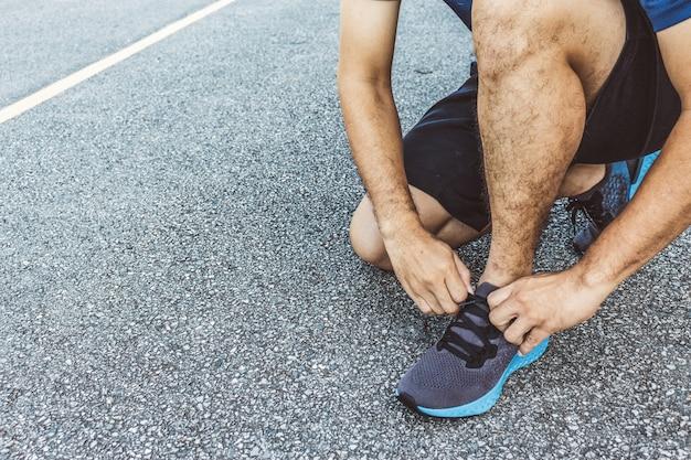 Спортсмен крупным планом, связывая кроссовки
