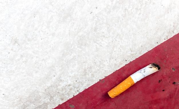 タバコの日の概念はありません。セメント道路の背景にタバコ