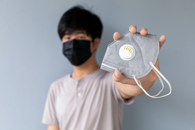 若い男のクローズアップ手は感染性コロナウイルスに対するマスクを与える
