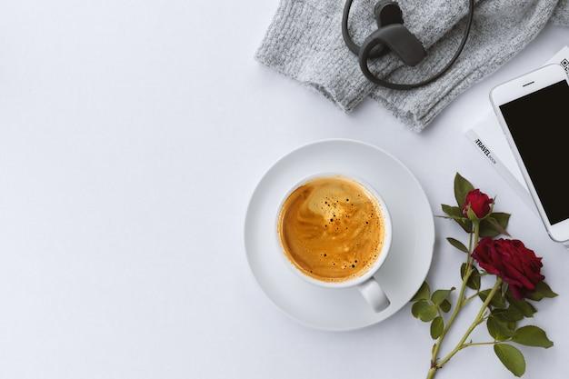 冬のコンセプト。一杯のコーヒー、スマートフォン、バラの花、白いテーブル背景にセーター。上面図