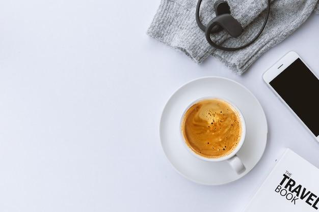 冬のコンセプト。白いテーブルの背景にセーターとコーヒーのカップ。上面図