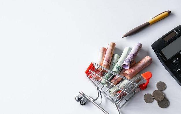 Калькулятор, ручка и корзина с деньгами (тайские деньги) внутри вверх ногами на белом. вид сверху