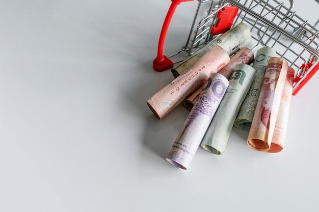 Магазинная тележкаа с деньгами (тайскими деньгами) внутри вверх ногами на белизне. вид сверху