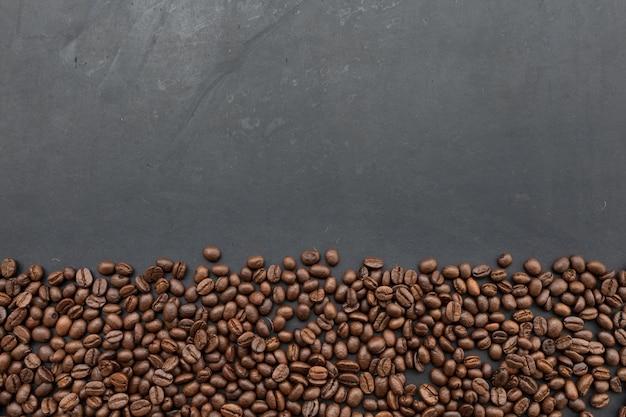 Кофейные зерна на черной стене деревянного стола. вид сверху