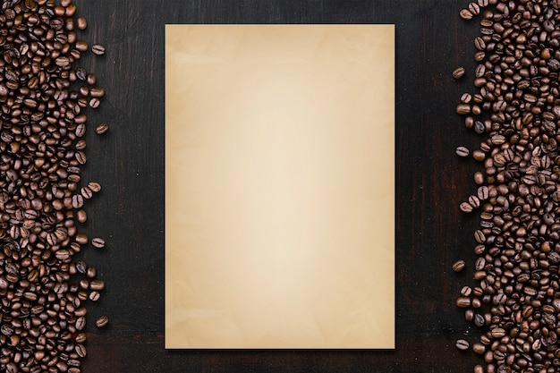 黒い木のテーブルの上にコーヒー豆とヴィンテージペーパー