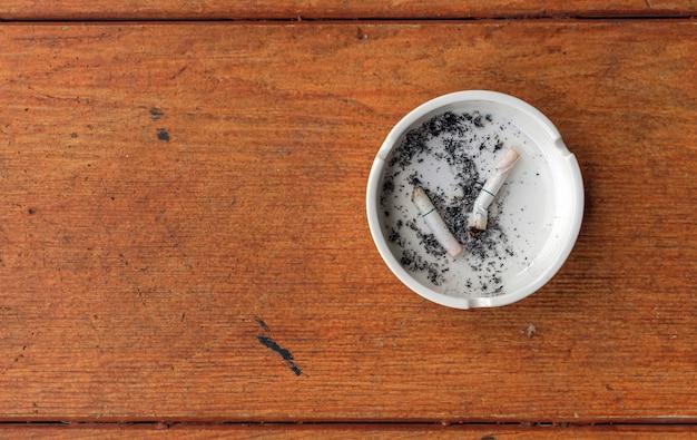 Макрофотография белая пепельница на деревянном фоне с подсветкой в фоновом режиме