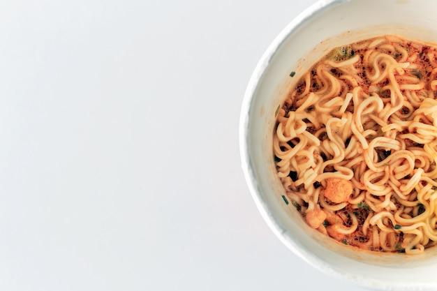 Макрофотография мама или лапша в чашке и томям суп на белом столе