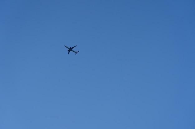 青い空に飛ぶ商業飛行機