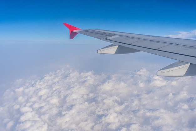 美しい雲の上を飛んでいる飛行機の翼