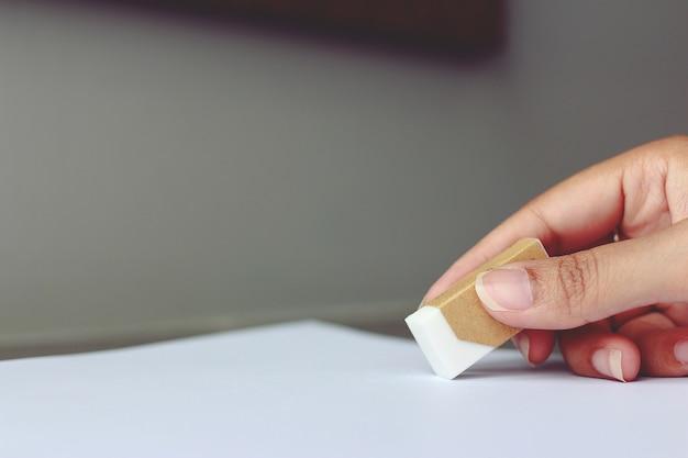 手が紙に間違ったものを消去するための消しゴムを保持