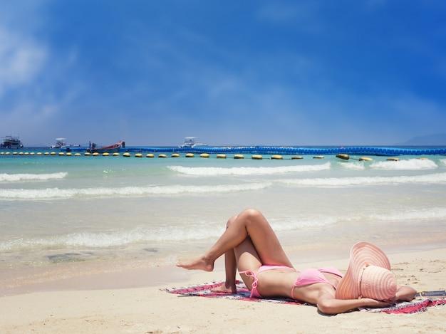 ビーチでビキニを着ている女性、サンデッキの座席。ビーチでリラックス
